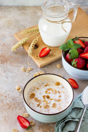 Healthy breakfast - whole grain flakes, milk and fresh strawberries on stone or slate background. The concept of nutrition health. Copy space. Фото со стока