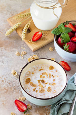 Healthy breakfast - whole grain flakes, milk and fresh strawberries on stone or slate background. The concept of nutrition health.