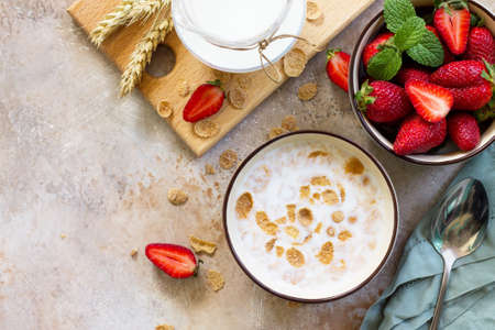 Healthy breakfast - whole grain flakes, milk and fresh strawberries on stone or slate background. The concept of nutrition health. Copy space, top view flat lay background.