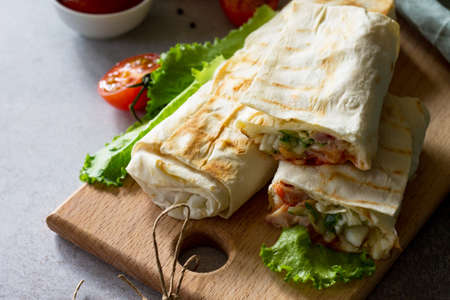 Shaurma, cut in half, shaurma doner, meat with vegetables in a bread cake, on a light stone or concrete background. Concept restaurant fast food.