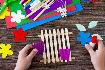 The child glues the details of the gift of summer flowers on wooden sticks fence. Handmade. Project of children's creativity, handicrafts, crafts for kids.