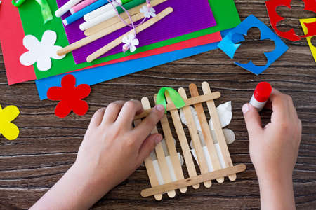Colored paper, glue, sheets, ribbons, flowers for making a gift summer flowers on wooden sticks fence. Handmade. Project of children's creativity, handicrafts, crafts for kids. Фото со стока