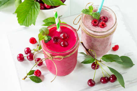 Raspberry and Cherry milkshake or smoothie on a white wooden background. Healthy juicy vitamin drink diet or vegan food concept. Stock Photo