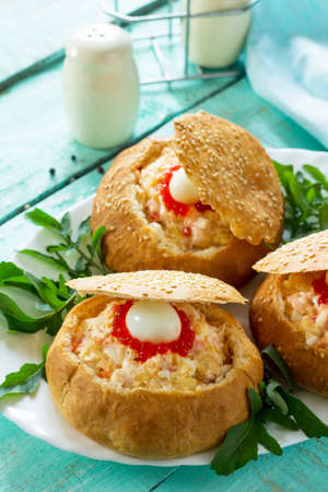 Snack on the festive table. Bun stuffed with shrimp salad and red caviar. Stock Photo