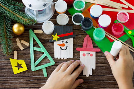 The child glues the parts Christmas decoration or Christmas gift. Handmade. Project of children's creativity, handicrafts, crafts for kids.
