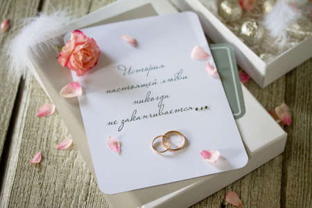 Two Golden Wedding Rings, box of chocolates and a wedding invitation, an inscription that the story of true love never ends. Copy space. Foto de archivo