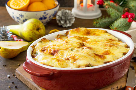 Potato gratin with pear, raclette cheese, and bacon on a festive Christmas table.Traditional french cuisine.
