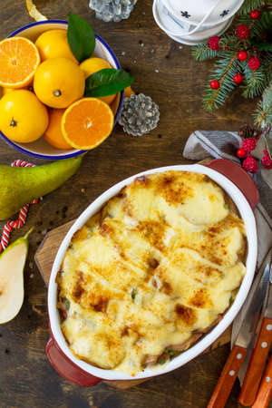 Potato gratin with pear, raclette cheese, and bacon on a festive Christmas table.Traditional french cuisine. Top view flat lay background. Copy space.