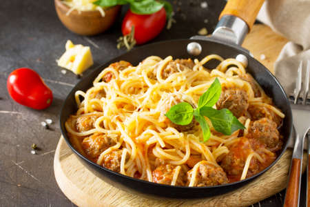 Spaghetti with Meatballs with Tomato Sauce and Parmesan Cheese on a dark stone or concrete background. Stock Photo