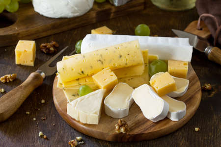 Cheese plate. Assortment of cheeses, grapes and nuts on dark rustic wooden table. Stock Photo