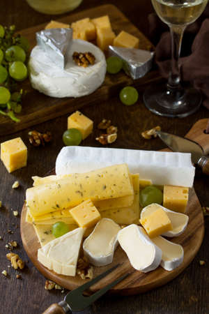Cheese plate with grapes,  wine glass and nuts on dark rustic wooden table.