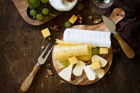 Cheese plate. Assortment of cheeses, grapes and nuts on dark rustic wooden table. Top view flat lay background. Copy space.
