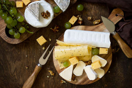 Cheese plate. Assortment of cheeses, grapes and nuts on dark rustic wooden table. Top view flat lay background. Stock Photo
