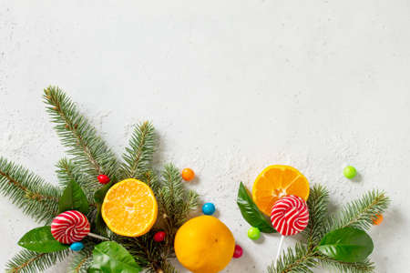 Fresh and Juicy Tangerines, Spruce branches, Snow, and a variety of Christmas sweets on stone or concrete table.