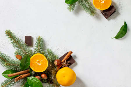 Fresh and Juicy Tangerines, Spruce branches, Snow, and various Christmas Ingredients for Baking on stone or concrete table. Stock Photo