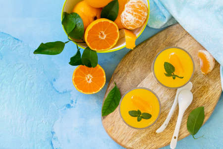 Panna cotta with tangerines jelly and mint, Italian dessert, homemade cuisine. Top view flat lay background. Copy space. Stock Photo