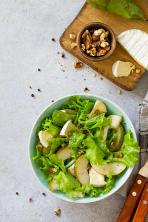Pear Salad, Walnut, Camembert Cheese and Vinaigrette Dressing on stone table. Traditional french cuisine. Traditional french cuisine. Top view flat lay background. Copy space.