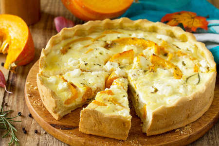 Classic Quiche Lorraine Pie with Pumpkin and Feta Cheese on a wooden table.