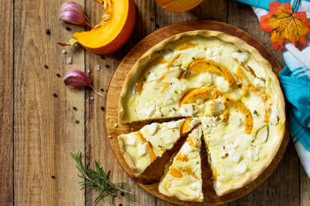 Classic Quiche Lorraine Pie with Pumpkin and Feta Cheese on a wooden table. Top view flat lay background. Copy space.