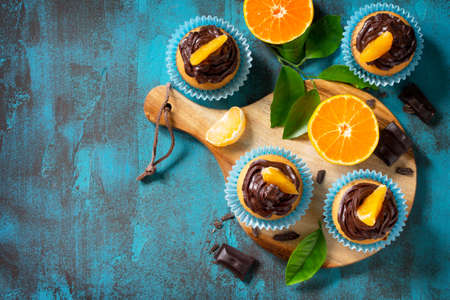 Orange Cupcakes with Chocolate Cream and Fresh Tangerines on a blue stone or concrete table. Top view flat lay background. Copy space.