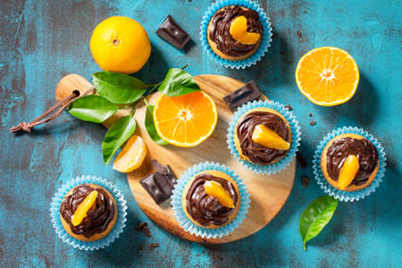 Orange Cupcakes with Chocolate Cream and Fresh Tangerines on a blue stone or concrete table. Top view flat lay background.