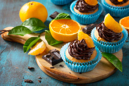 Orange Cupcakes with Chocolate Cream and Fresh Tangerines on a blue stone or concrete table. Stock Photo