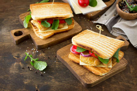 Sandwich with Tomatoes, Cheese, Crispy Chicken Nuggets and Arugula. Delicious fresh homemade club sandwich with chicken on a wooden table. Fast food. Copy space. Stock Photo