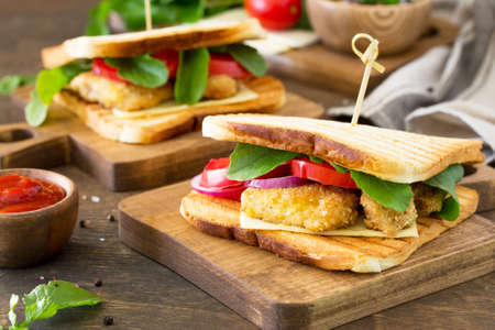 Sandwich with Tomatoes, Cheese, Crispy Chicken Nuggets and Arugula.  Delicious fresh homemade club sandwich with chicken on a wooden table. Fast food.