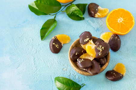 Slices of Tangerines in Chocolate. Dessert Tangerines on a blue stone or concrete background. Copy space.