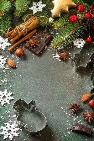 Ingredienti per la cottura del pan di zenzero di Natale - cioccolato, cannella, anice e noci su fondo scuro di pietra o ardesia. Stagionale, sfondo alimentare. Copia spazio.