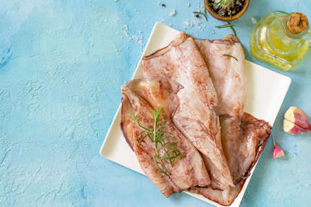 Fresh Squid, Various Spices and Olive Oil on blue concrete or stone table. Top view flat lay background. Stockfoto