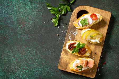 Italian Antipasti snacks set for Wine. Variety Brushetta with Soft Cheese, Pear, Radish, Salmon and Dried Tomatoes served on a rustic wooden board on a stone table. Top view flat lay background. Copy space.