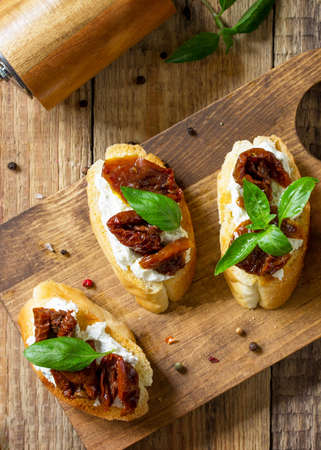 Italian Antipasti snacks for Wine. Brushetta with Soft Cheese and Dried Tomatoes on a wooden table. Top view flat lay background. Banque d'images