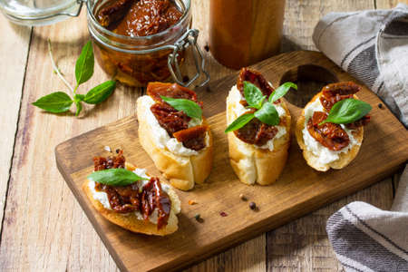 Italian Antipasti snacks for Wine. Brushetta with Soft Cheese and Dried Tomatoes on a wooden table. Banque d'images