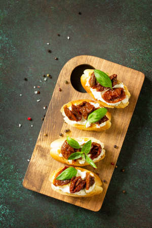 Italian Antipasti snacks for Wine. Brushetta with Soft Cheese and Dried Tomatoes served on a rustic wooden board on a stone table. Top view flat lay background. Copy space.