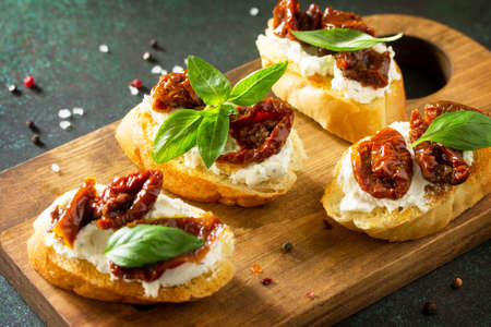 Antipasti snacks for Wine. Brushetta with Soft Cheese and Dried Tomatoes served on a rustic wooden board on a stone table. Фото со стока