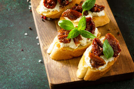 Italian Antipasti snacks for Wine. Brushetta with Soft Cheese and Dried Tomatoes served on a rustic wooden board on a stone table. Copy space. Banque d'images