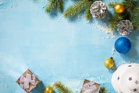 Christmas fir branch, lantern and gifts on a blue stone background. Top view flat lay background. Copy space.