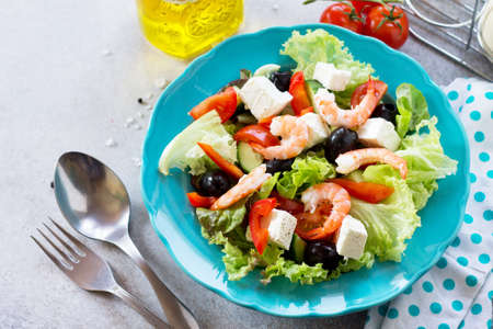 The concept of healthy and dietary food. Greek salad with shrimps and vegetables on a light stone or slate table.