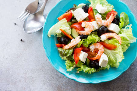 The concept of healthy and dietary food. Greek salad with shrimps and vegetables on a light stone or slate table. Copy space.