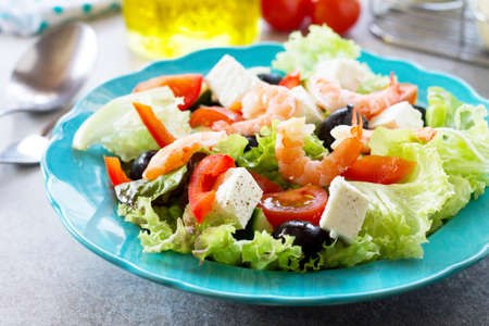 The concept of healthy and dietary food. Healthy salad close-up, Greek salad with shrimps and vegetables on a light stone or slate table. Stock Photo