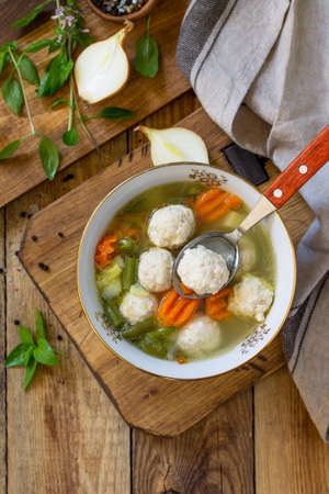 The concept Diet menu. Healthy soup with vegetables and chicken meatballs in a bowl on wooden table in rustic style. Top view flat lay background. Copy space.