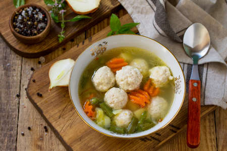 The concept Diet menu. Healthy soup with vegetables and chicken meatballs in a bowl on wooden table in rustic style. Stock Photo