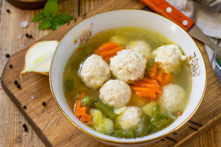 The concept Diet menu. Healthy soup with vegetables and chicken meatballs in a bowl on wooden table in rustic style. Soup close-up.
