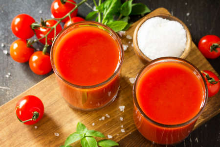 Diet nutrition concept. Glasses with tomato juice close-up and fresh tomatoes on a dark stone table. Stock Photo
