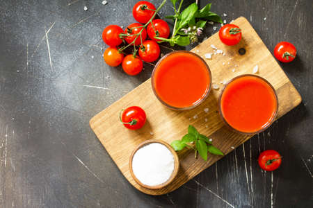 Diet nutrition concept. Glasses with tomato juice and fresh tomatoes on a dark stone table. Top view flat lay background. Copy space.