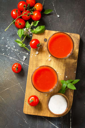 Diet nutrition concept. Glasses with tomato juice and fresh tomatoes on a dark stone table. Top view flat lay background.