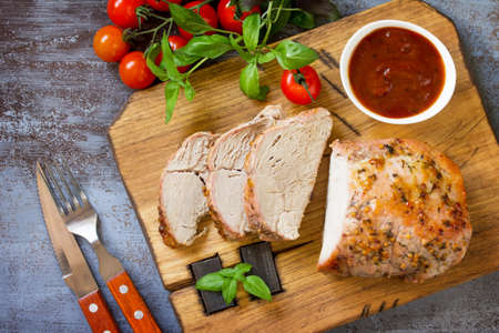 Baked Meat. Roast pork Meat with honey-mustard glaze served with ketchup on a dark stone table. Top view flat lay background.
