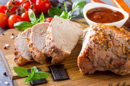 Baked Meat close-up. Roast pork Meat with honey-mustard glaze served with ketchup on a dark stone table. Stock Photo