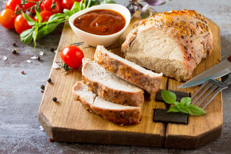 Baked Meat. Roast pork Meat with honey-mustard glaze served with ketchup on a dark stone table.
